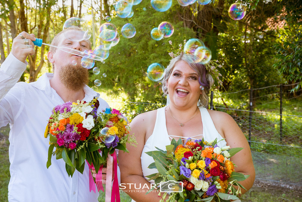 Bride and Groom blowing bubbles after cermony at home wedding in Elimbah