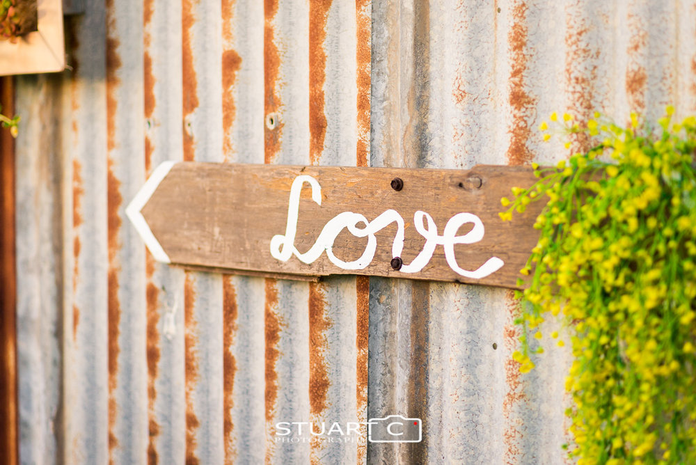 Rustic hand painted love sign on tin wall at home wedding in Elimbah