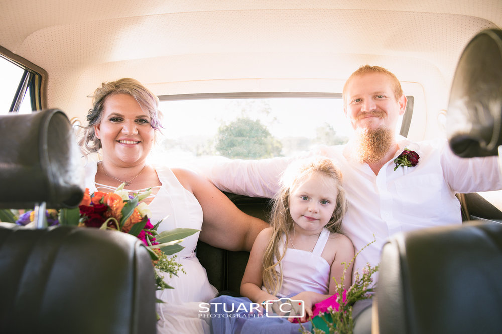 portrait of bride and groom with daughter in the backseat of wedding car after the ceremony, Elimbah Caboolture