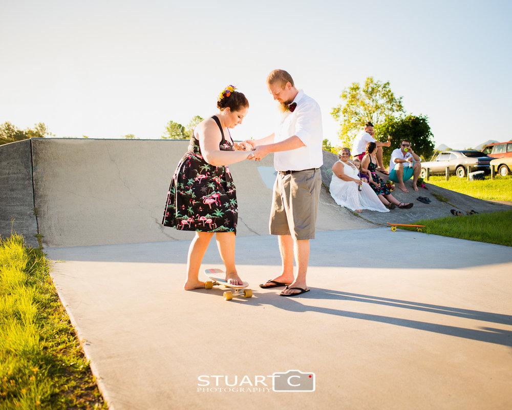 Groom and Bridesmaid on skateboard with wedding party behind at skatepark in Elimbah