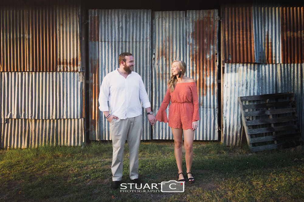 Full length portrait of newly engaged couple Jannika and Matt standing in front of rustic tin wall in the town of Woodford