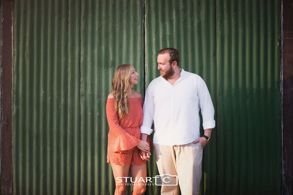 Urban Rustic Portrait of newly engaged couple Jannika and Matt in front of a green tin wall near the main street of woodford