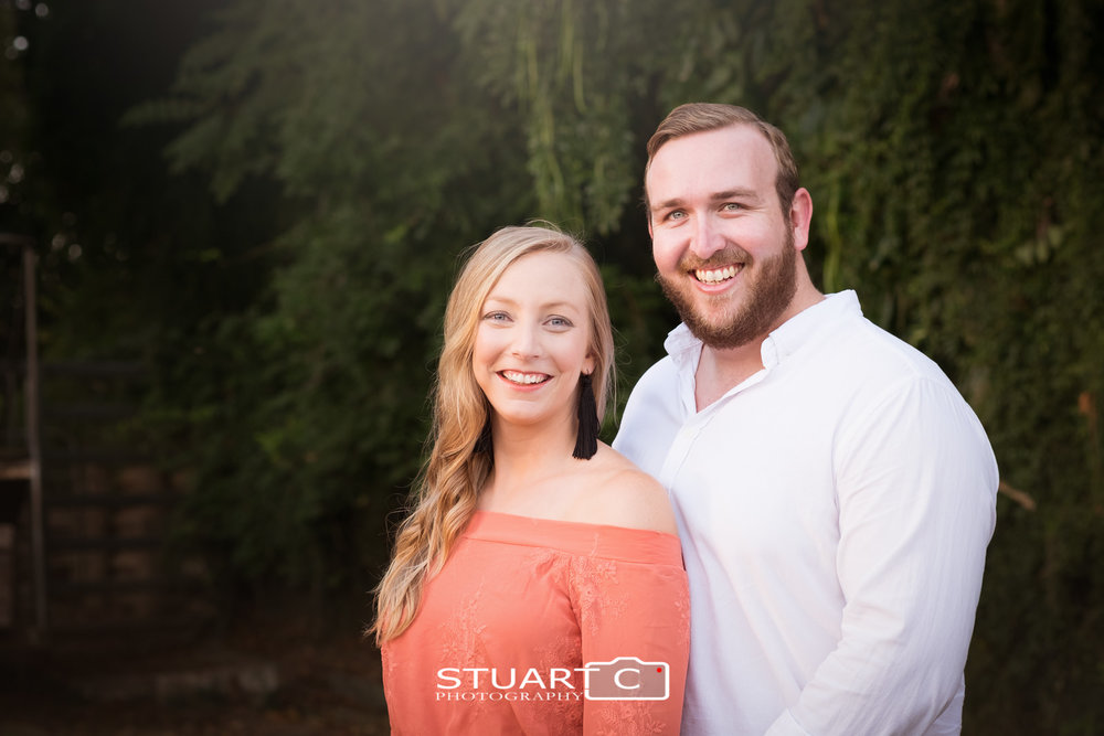 Close up Portrait of newly engaged couple Jannika and Matt against dark green background in the main street of woodford