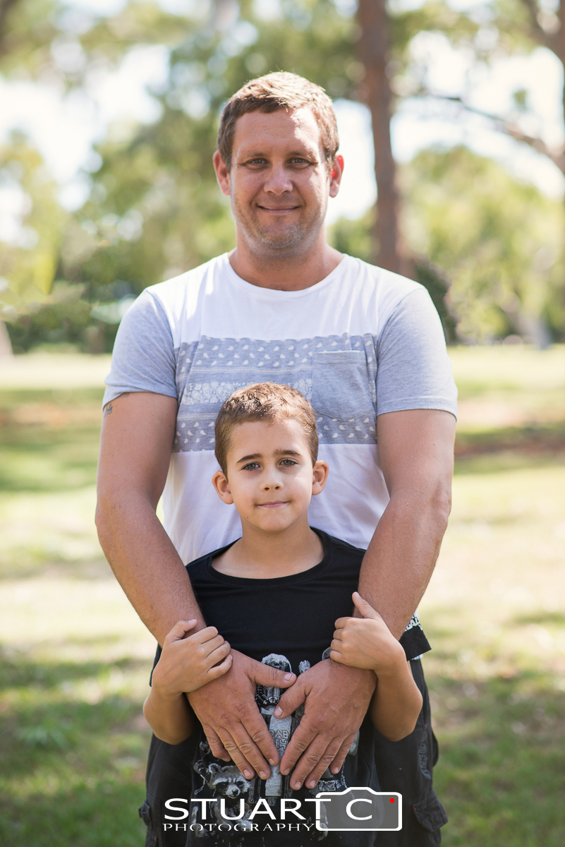 father and son standing together during outdoor family portraits in Clayton Park Beachmere