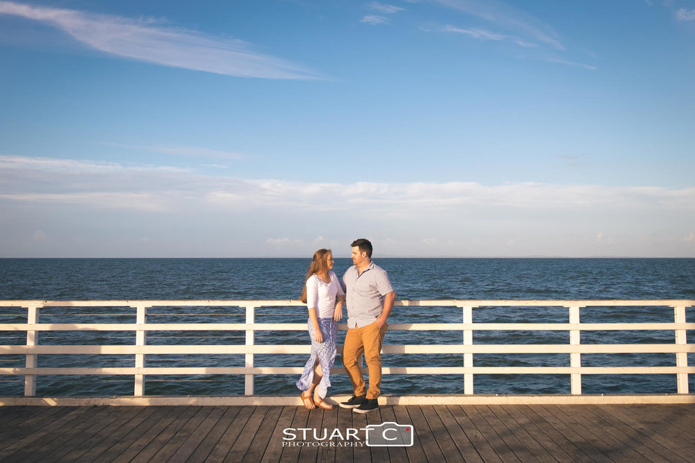 Wide environmental portrait of Engaged couple standing against white handrails at the end of Shorncliffe Pier with blue sky and clouds behind