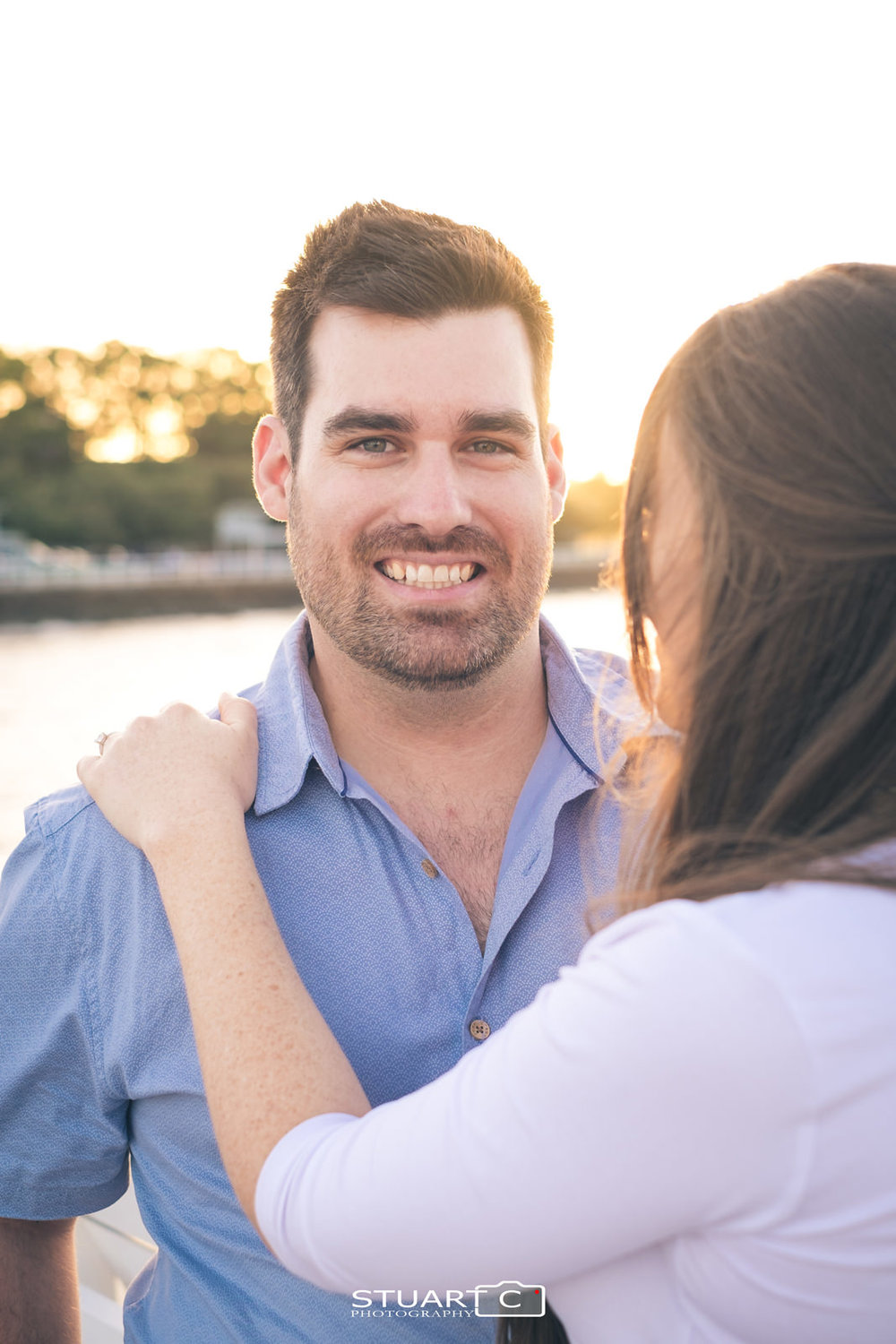 Close up portrait of guy standing on shorncliffe pier with his fiance standing looking towards him during afternoon engagement photo shoot