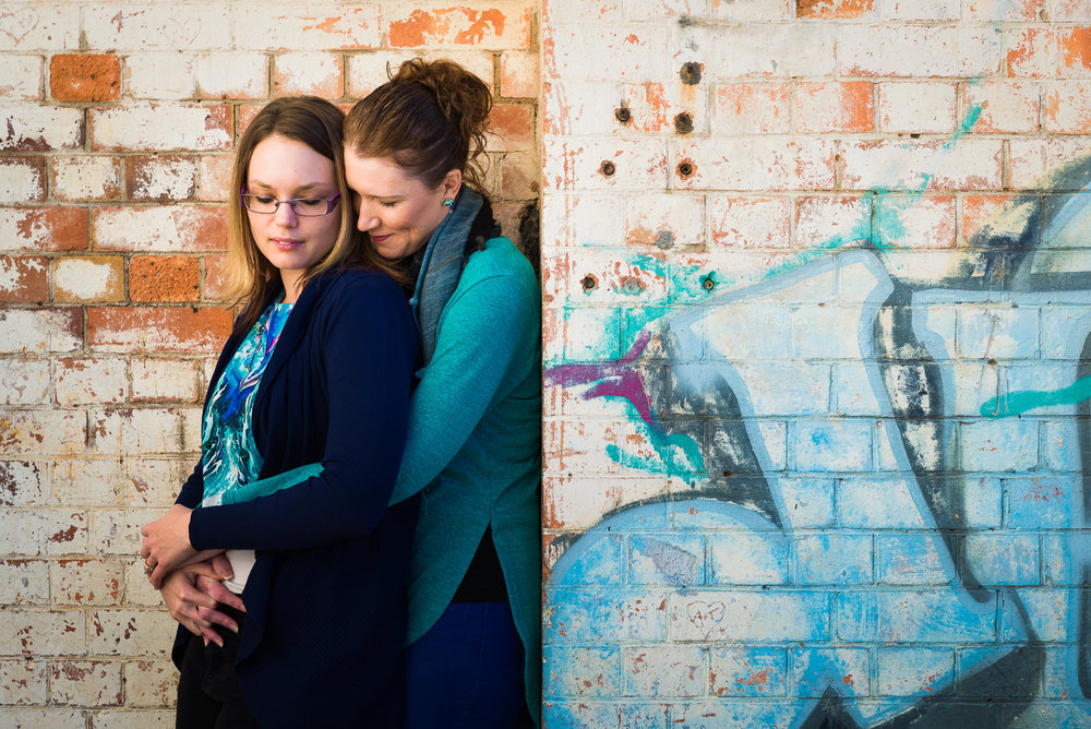 LGBQTI engaged couple at brisbane powerhouse standing in front of brick wall with graffiti