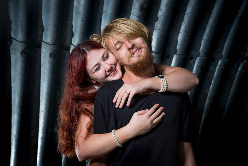engaged couple embracing in dark urban setting