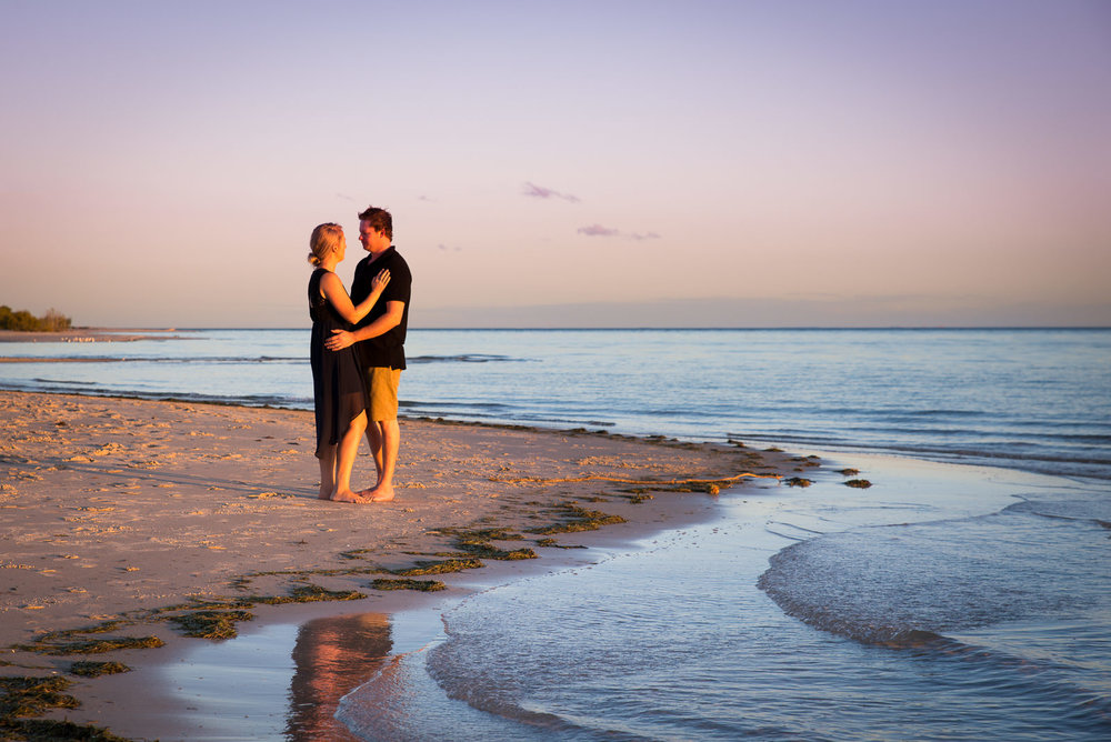 Engaged couple embracing on the beach at Bribie Island during sunset
