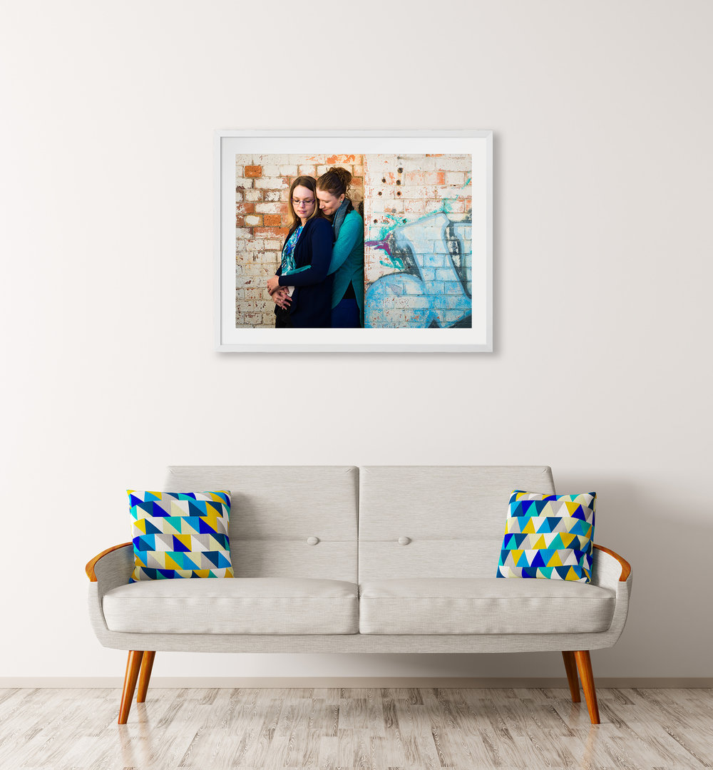 Framed engagement portrait above couch in lounge room