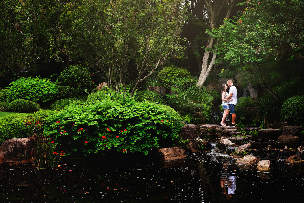 engaged couple standing on stepping stone in front of Japanese lake at Mt Cootha Botanical Gardens