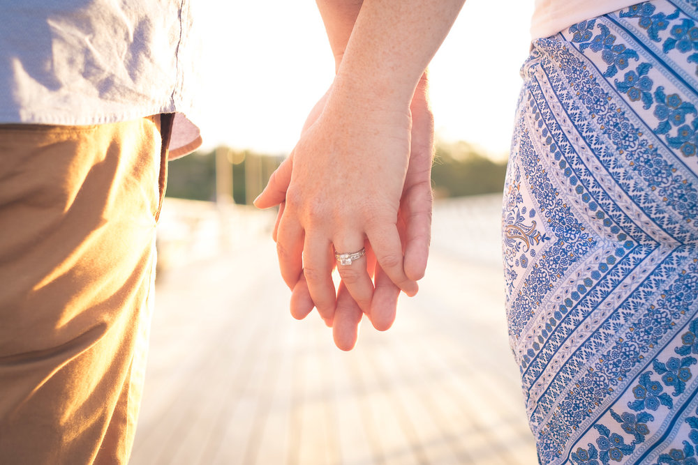 engaged couple holding hands walking walking shorncliffe pier in golden light