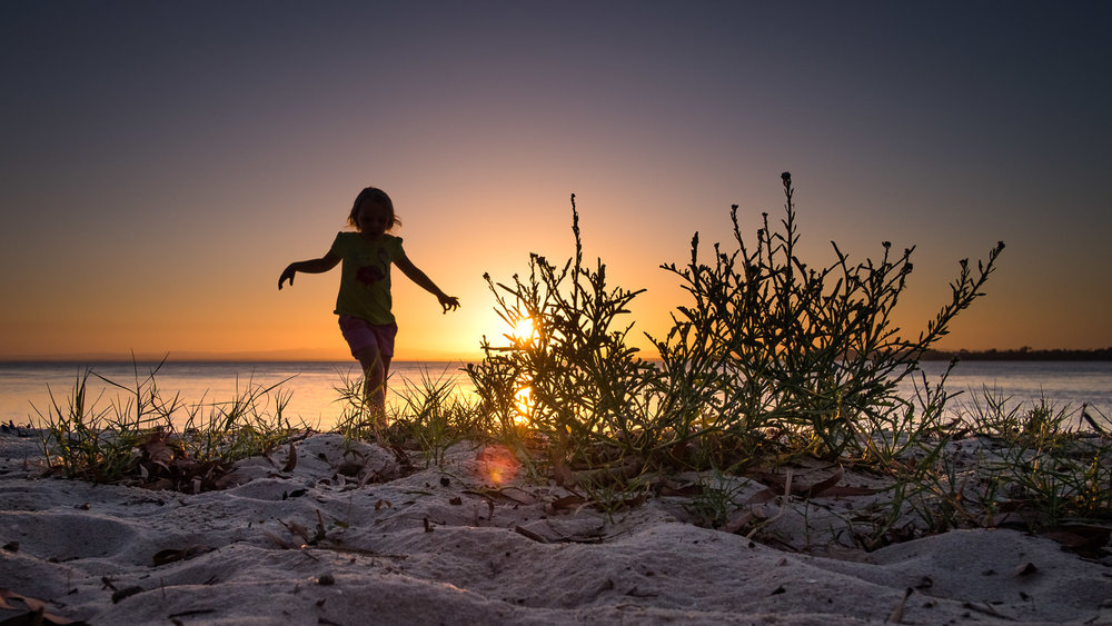 candid natural action portrait of young girl running over dunes during sunset at Bribie Island