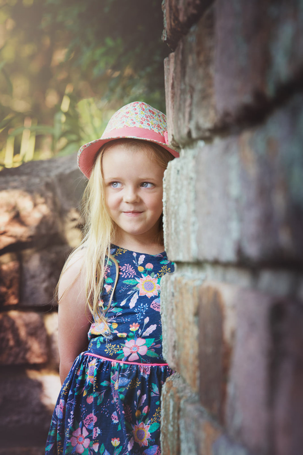 portrait of young girl standing against urban stone wall