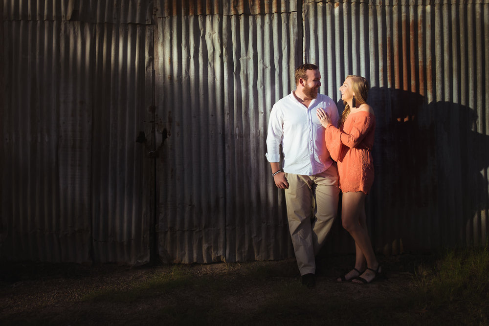 engaged couple standing in pocket of light against rusted tin wall in Woodford