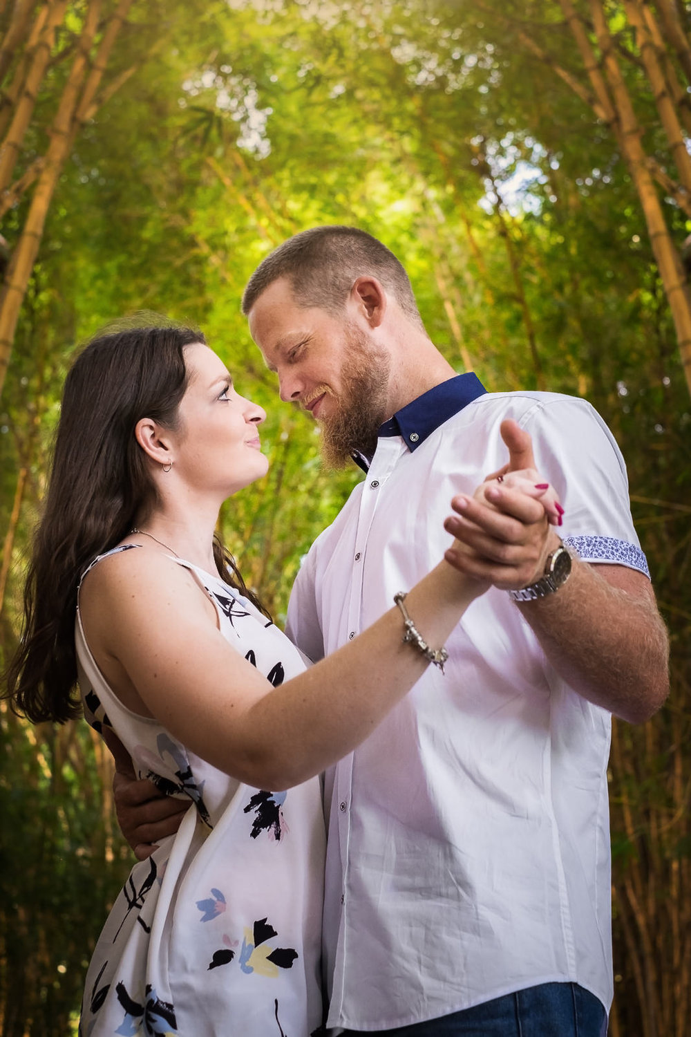 Engaged couple wearing white and blue complimentary shirts for portrait session in gardens