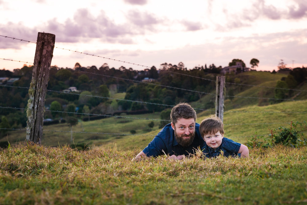 father and son playing a game in the grass during family photo session at maleny
