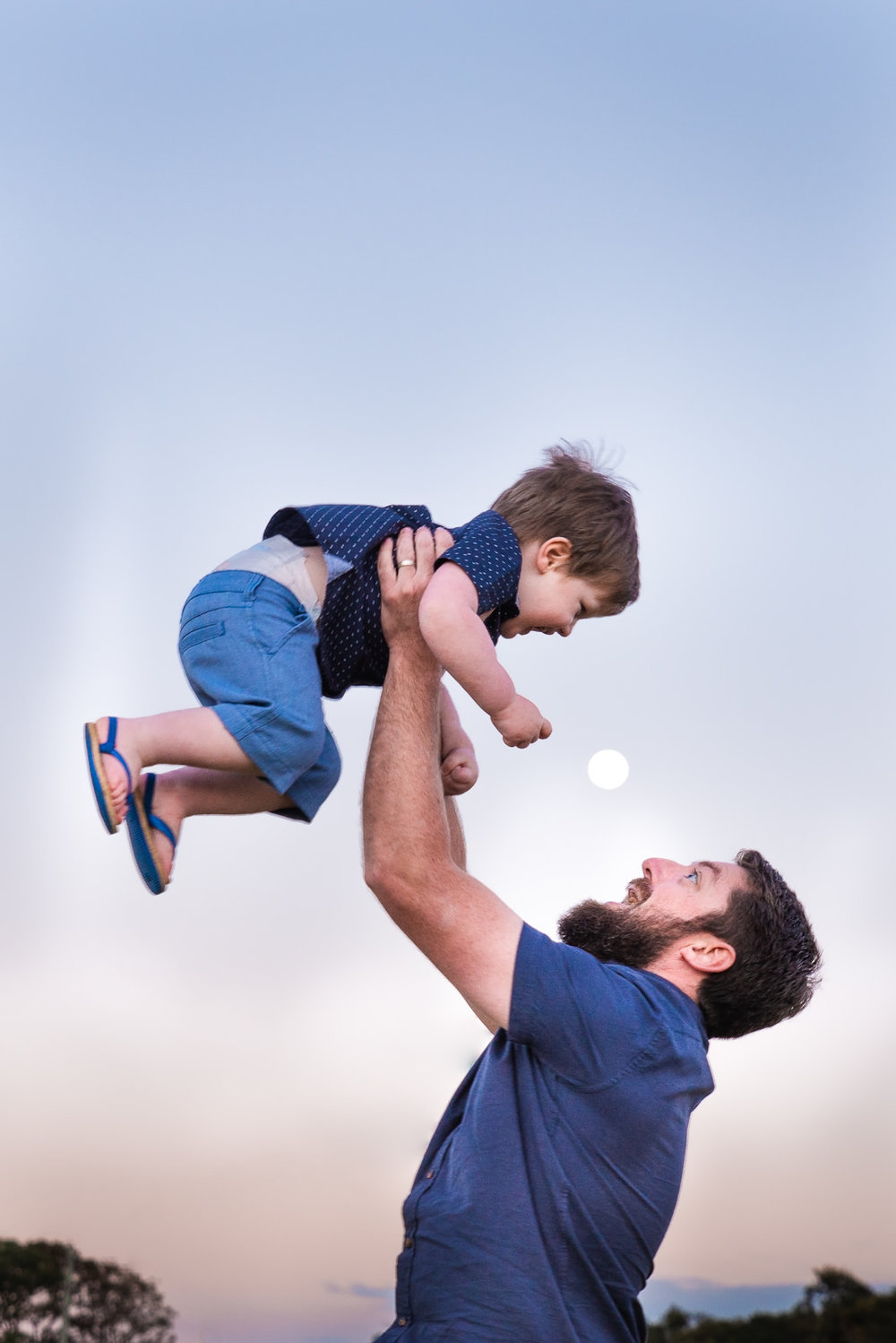 father throwing son in the air with the moon in background during sunset family photo session at maleny
