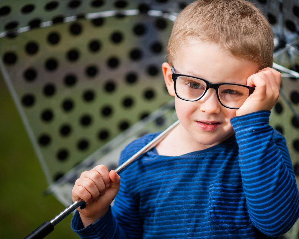 Close up portrait of boy with glasses holding an umbrella in the rain | Caboolture outdoor family photos