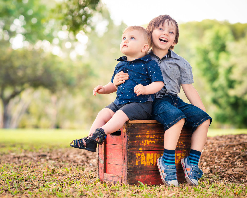family portrait of brothers sitting on a vintage timber crate at Centenary lakes Caboolture