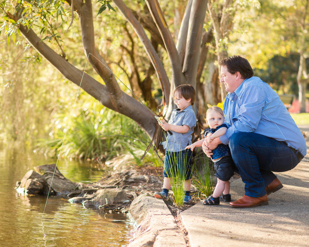 Dad and sons pretending to fish at Centenary Lakes Caboolture