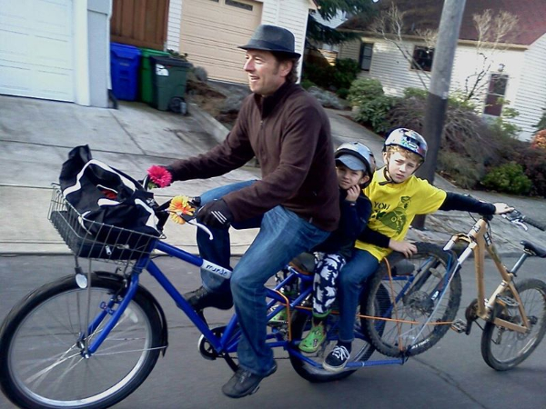 Robert Ping, WALC Institute's Executive Director, bikes home from school with his sons.