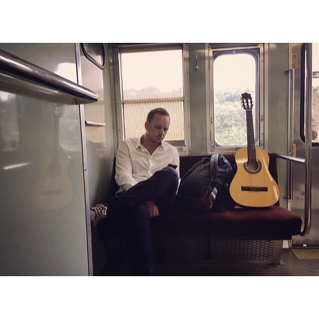 Payne on a train. En route to Tottori, Japan. Prepared with our consignment store guitars for any spontaneous performance that might occur.
