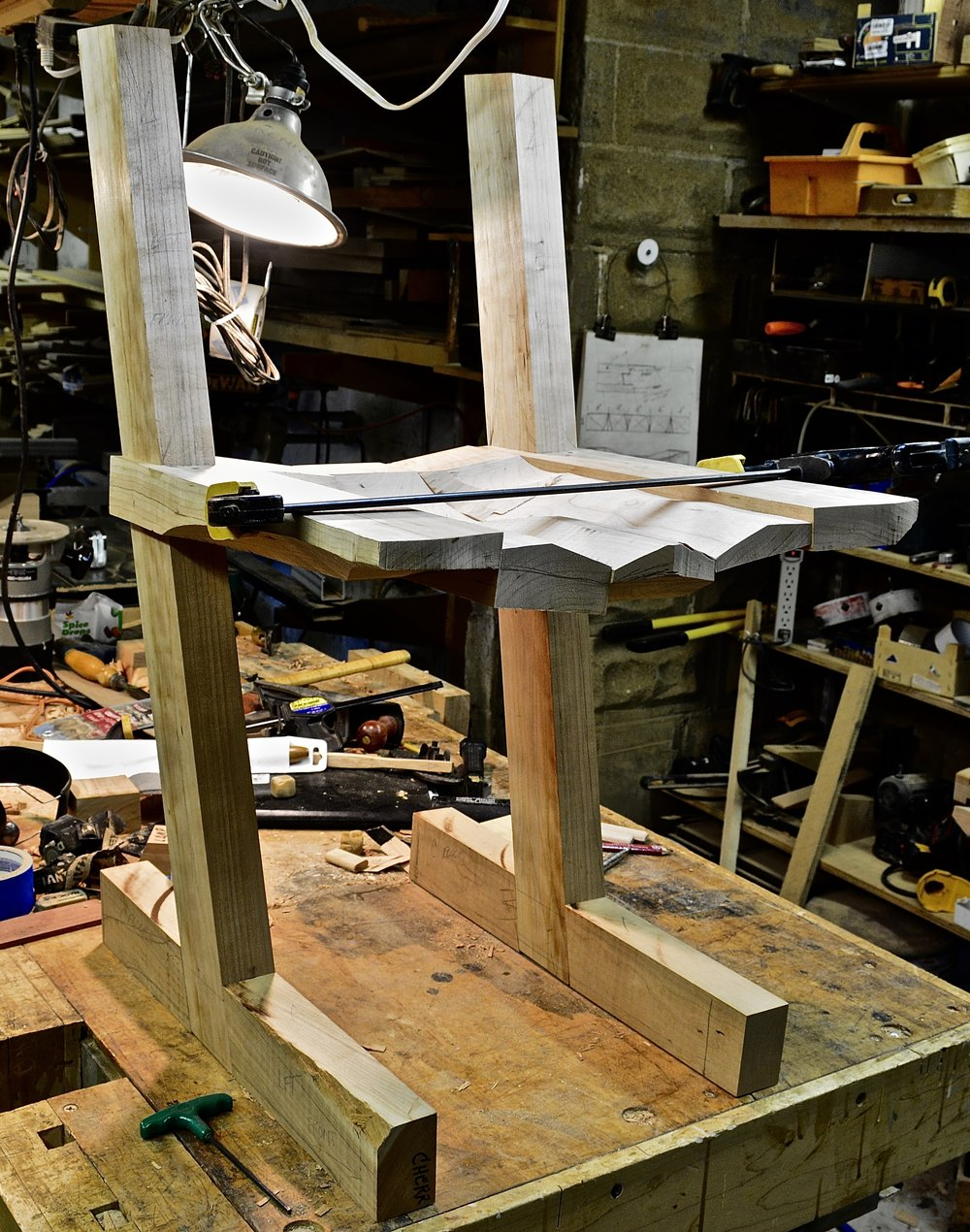 I've bandsawn the rough shape of the seat, the leg - seat joint has been fitted, and the leg-foot bridle joint has been fitted.  Now I take it apart (again,and again, and again), bandsaw the rough shape of the legs and feet and glue up the seat.