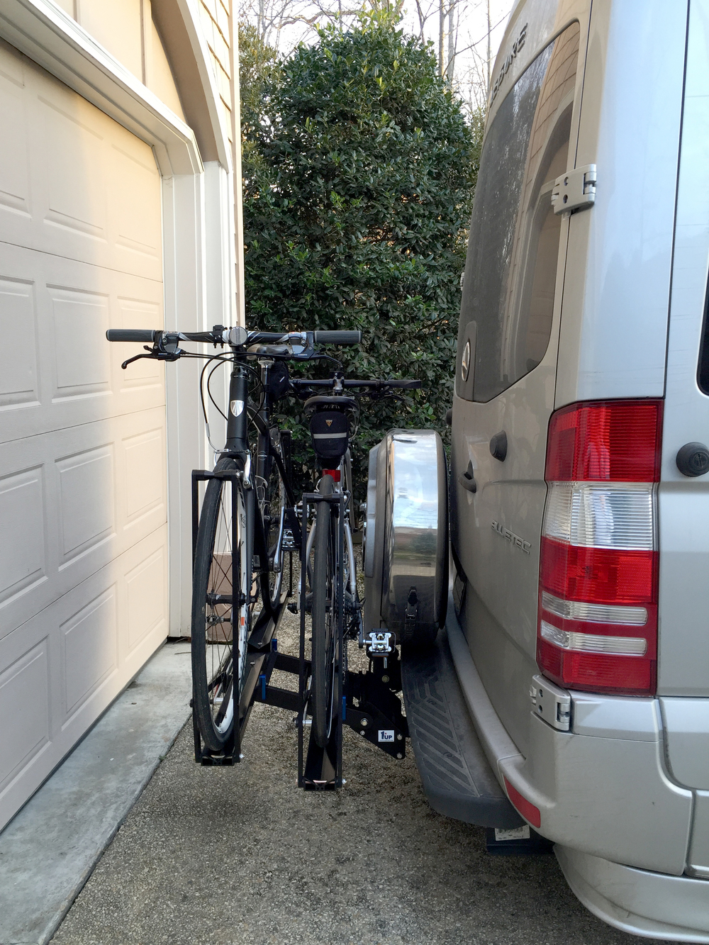 Bikes clear the spare tire carrier on the Free Spirit.  Without the bikes mounted, you can  fold up the rack  only if you add a  hitch extender .
