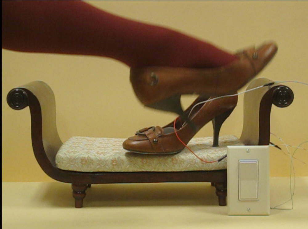 video still: Untitled: 2 shoes, 1 leg, small furniture, and a switch