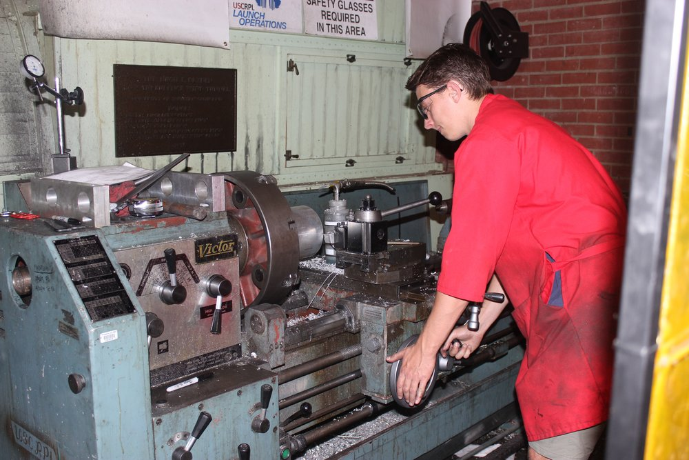 Brady Runyon machining a aluminum nozzle carrier on the lathe