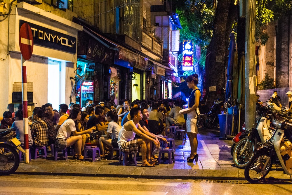 Beating the heat by eating and drinking on the streets of Hanoi, Vietnam on tiny stools.