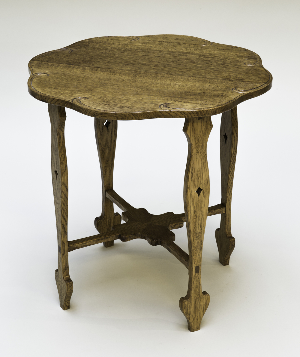 "This piece is based on a Charles Rohlfs table. An interesting feature of this table is the bottom stretcher, which is mortised and tenoned into the legs. The stretchers are joined to each other with a mitered half lap joint. Quarter sawn white oak is the wood used for this table. Blonde and amber shellac was used to even out the wood color. Brown glaze was applied to highlight the grain and to give the table an aged look. An oil and urethane finish was used for a top coat. You can purchase this table for $600.00. Dimension: 24"" diameter x 24"" high    (Click on the picture to see how it was put together.)"