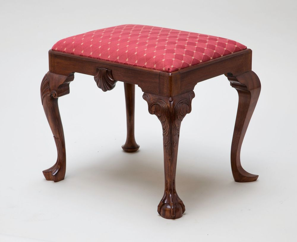 "This Georgian footstool is unique in that it has four different style legs, popular for that period. Mahogany is the primary wood, pine was used for glue blocks and ash for the slip seat frame. The legs are mortised and tenoned to the rails. The shell was carved and then applied to the rail.  A formula of orange dye, brown walnut dye, brown walnut pigmented stain were used to achieve the rich color. A shellac was applied by hand (French polish).   Muslin, horse hair, two inch webbing, black cloth and cotton stuffing are use for the slip seat cushion. Price $1800.00. Dimension: 21"" wide x 17"" high x 17"" deep.     (Click on the picture to see how it was put together.)"