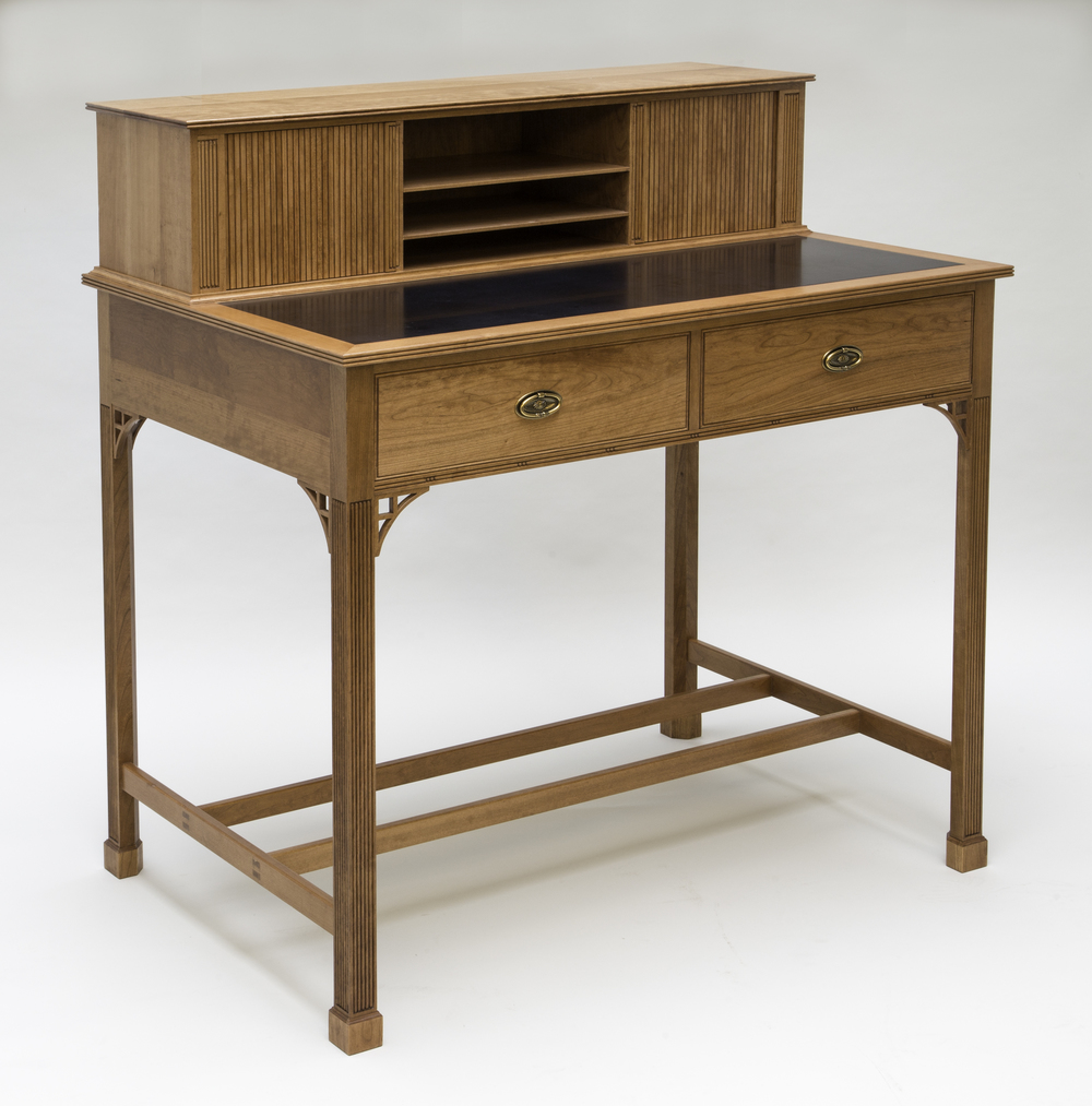 This Standing desk was designed for an open, unused space in our customer's kitchen, so that the laptop, mail, newspapers, fliers could be removed from the counters. The desk is appointed with many features found on more elegant pieces of furniture, such as reeded Marlborough legs with cuffed feet, brackets at the top of the legs, bead moldings around the writing surface and gallery top and tambour doors. Practicality and durability are also designed into this desk so that it will stand up to every day use.   It is 48 inches wide, 51 inches high and 31 1/2 inches deep. The writing surface is 40 inches from the floor, which is a comfortable standing working height of our customer. The primary wood is cherry and secondary wood pine. Cherry and rose wood were used for the gallery tambour doors. The writing surface is black satin Corian. Cherry stain and an oil/urethane finish were applied to give the desk a slightly aged cherry color.   A unique feature of this desk is that it can be placed anywhere in a room, against a wall, perpendicular to a wall, or in the middle of a room. Moldings continue all the way around the desk. All four legs have reeds, brackets and cuffed feet. The gallery back is a single piece of cherry veneered plywood held in place with moldings and grooves, no fasteners were used, which would detract from the appearance.  This desk has found a home. However, we would be glad to work with you to create one to fit your needs. Price as seen $6000.00.  We are thrilled this desk was selected to be in the Providence Journal on 10/31/2015 as part of an article on the 2015 Fine Furnishing Show in Pawtucket, RI. Click on the link below to read the article.   http://providencejournal.com/article/20151031/ENTERTAINMENTLIFE/151039961