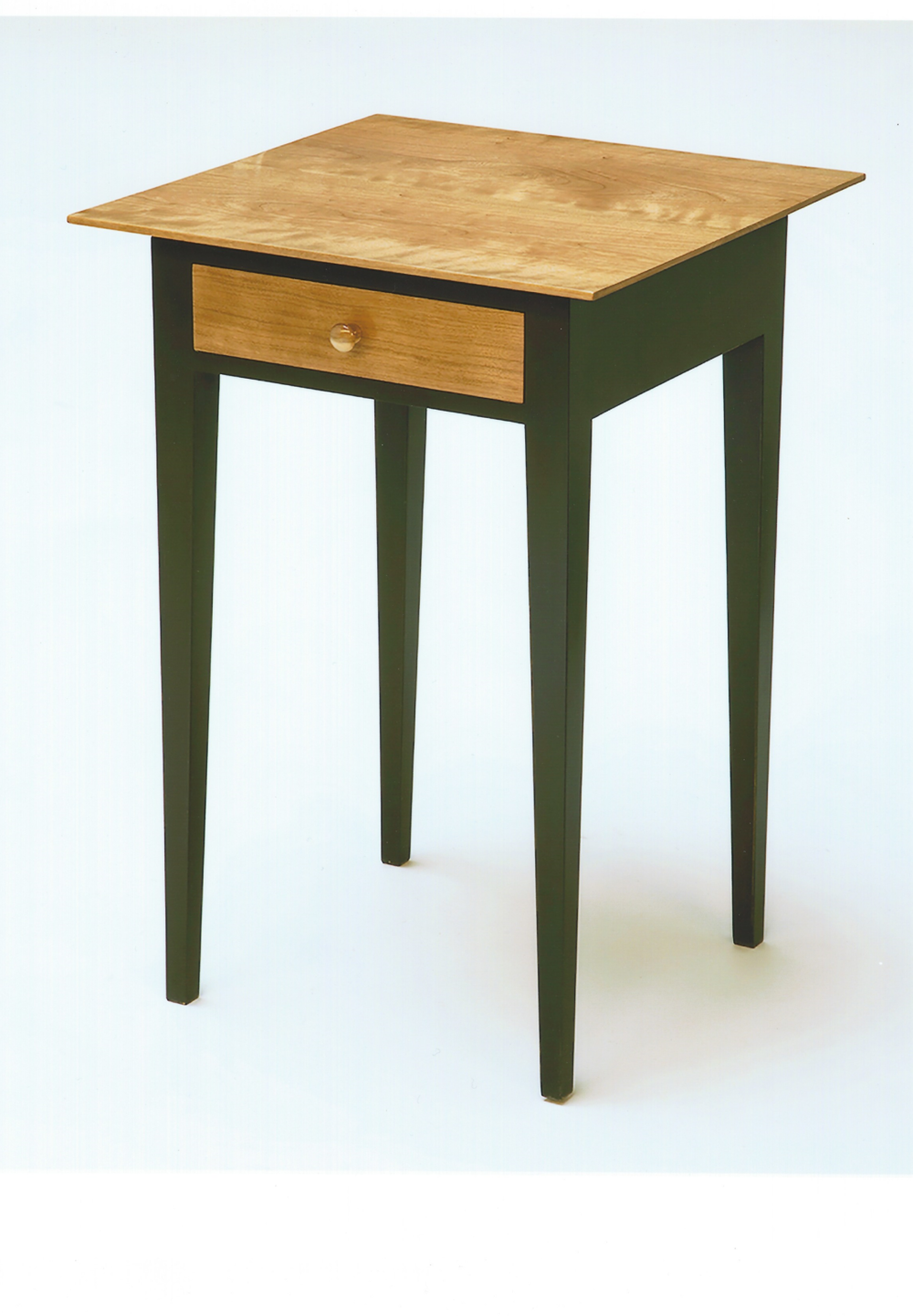 "This is a Shaker style nightstand with clean crisp lines. Cherry is used for the top, drawer front and knob. Poplar is used for legs, rails and drawer parts. Hand cut dovetails connect the front, back and sides of the drawer. The drawer bottom slides in a grove and is held in place by a single screw. Legs, sides and back are mortised and tenoned together. Cherry parts are French polished and poplar parts are finished with forest green milk paint with an oil and urethane top coat. This table is for sale at $450.00. Dimension: 26"" high x 18"" wide x 18"" deep."