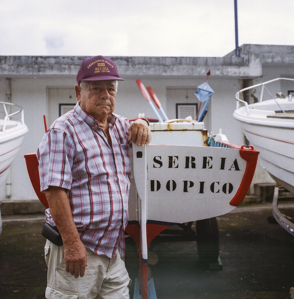 "José Dinis was born and raised within a family of whalers, having set foot on his dad's boat for the first time at the age of fourteen. "" At home we were eight siblings, six boys and two girls, my mother and my father. At a certain point in our family my dad, me and my five brothers formed the crew on a whaling boat. "". Here he stand in beside his boat ""Sereia do Pico"" (the Mermaid of Pico)."