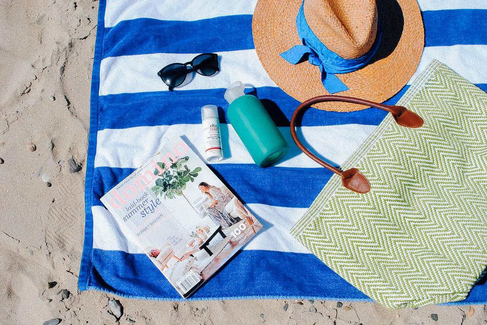 Dash & Albert Beach Bag(gifted) Striped Beach Towel. Sunglasses.  BKR Water Bottle.   Sunscreen.   Domino Magazine.  Lola Hat.