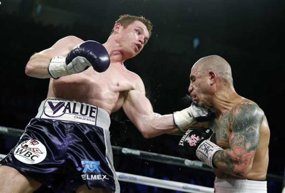 Canelo Alvarez land a smashing left hook to the chin of Miguel Cotto   Photo credit:Associated Press