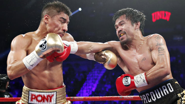 Manny Pacquiao lands on Jessie Vargas. Photo: Isaac Brekken/Associated Press