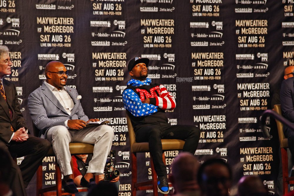 Floyd Mayweather sits and wait for Conor McGregor to finish his remarks before addressing the crowd in Los Angeles. Photo: Luis Mejia/Frontproof Media