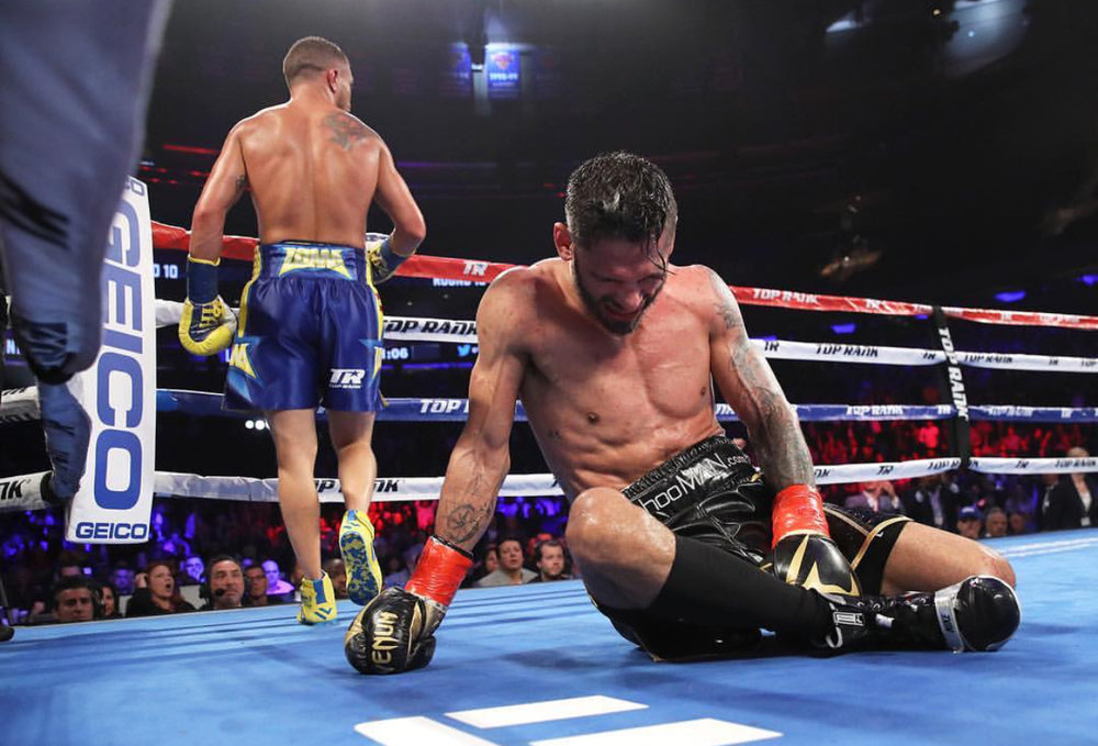 Jorge Linares on the canvas in pain after Vasiliy Lomachenko lands a perfectly placed body shot. Photo: Top Rank Boxing