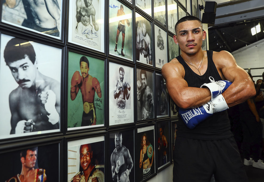 Teofimo Lopez poses next to a wall full of Hall-of-Fame fighters. Photo: Mikey Williams/Top Rank