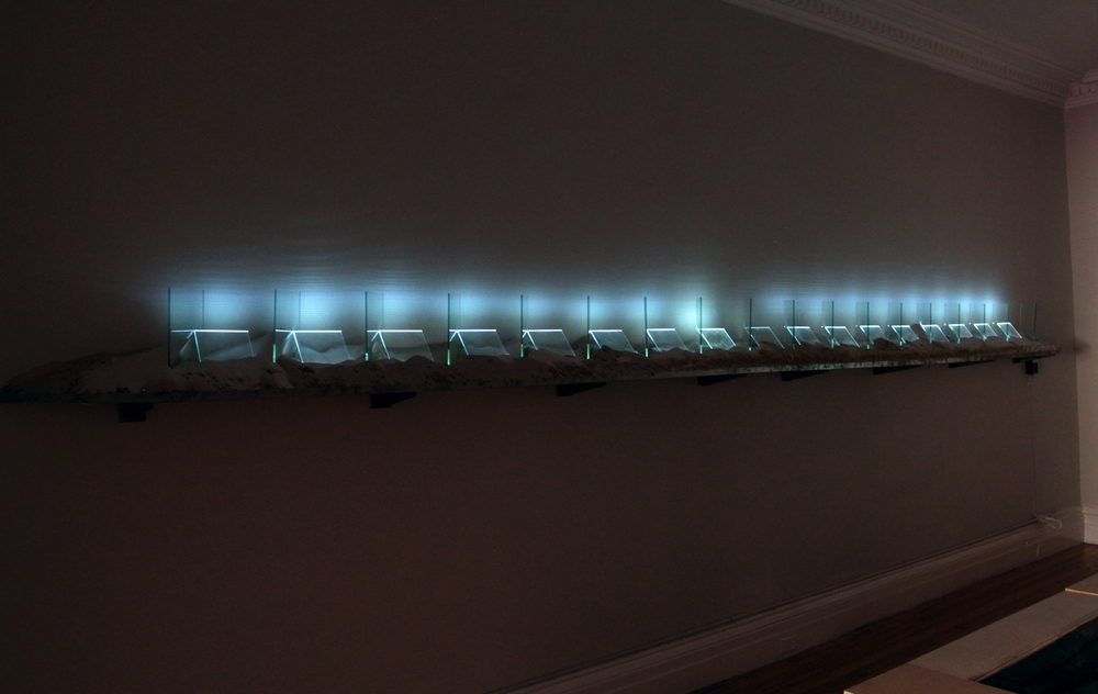 """Untitled    2013  Installation at Nyehaus Gallery in NYC  16"""" x 240"""" x 12""""  Steel shelf, sand, plate glass, argon with mercury, glass tubing, transformer"""