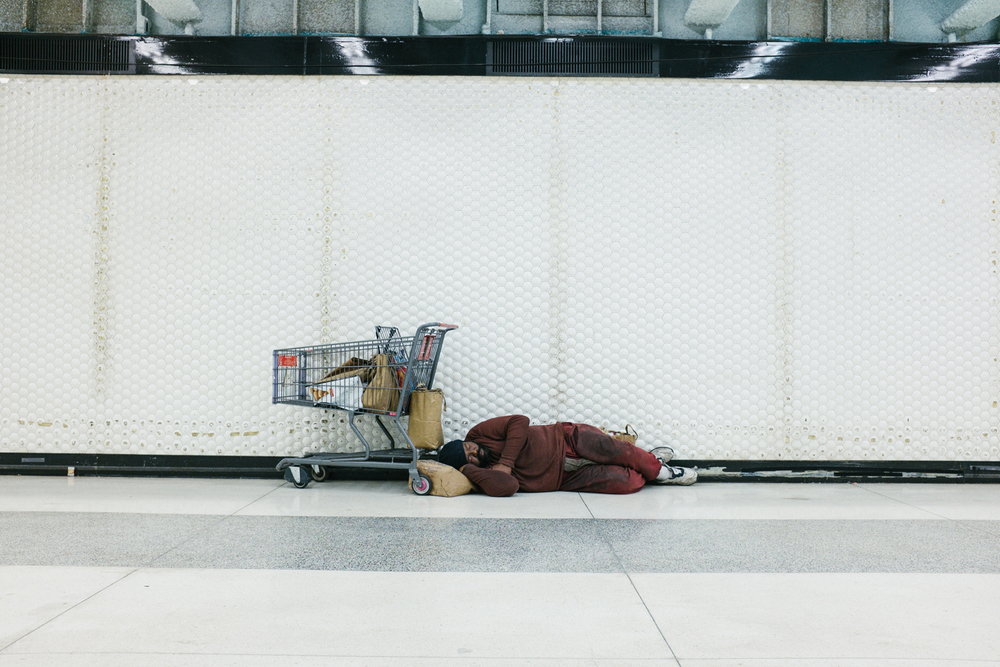 Sleeping man in Powell BART Station. You see a lot of homeless people further down the station where less tourists are as they don't get bothered as much.