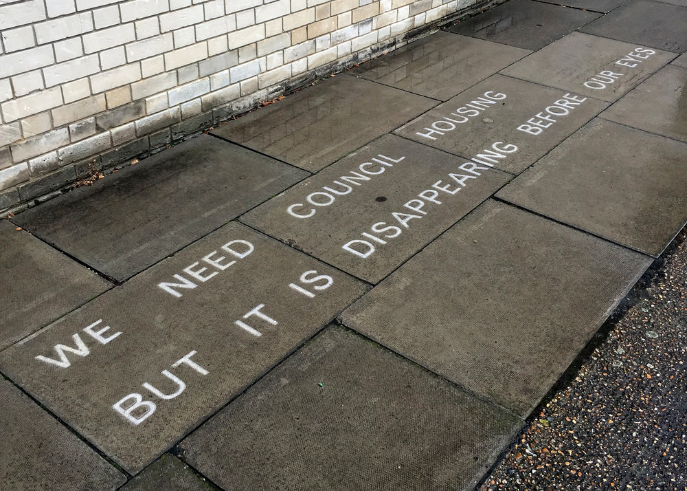We need council housing but it is disappearing before our eyes (2017), text in water-repellent spray (words by Susan), temporarily sited on Pelican Estate.