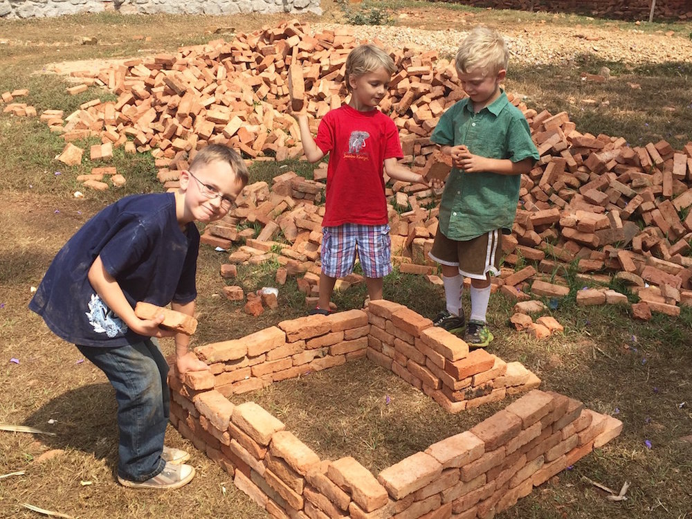 The boys make plans to begin construction on our house.  :)  Not really!  Just playing with some bricks with their new friend, Ben.
