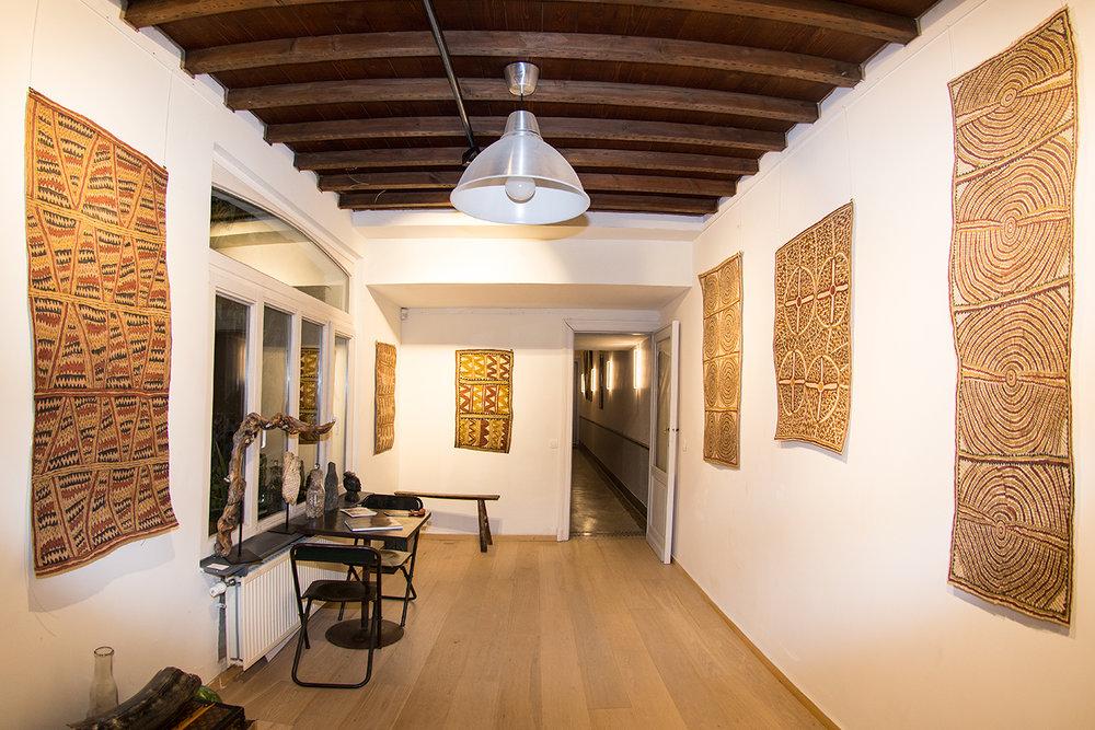 A gauche : une barkclothe de l'artiste Aspasia Gadai.Au fond : une étoffe d'écorce de l'artiste Dapeni Jonevari. Sur le côté gauche au fond, une œuvre de l'artiste Sarah Ugibari.A droite au milieu : œuvre de Penny-Rose Sosa. Sur les côtés gauche et droit,deux étoffes d'écorce de Dapeni Jonevari. © Photo : Aboriginal Signature • Estrangin Fine art gallery.