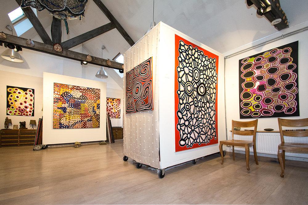 Vue de l'exposition d'art Aborigène Gems in a Patchwork jusqu'au 18 décembre à Bruxelles. De gauche à droite, une œuvre d'art Aborigène de l'artiste Myrtle Pennington (Spinifex), puis Taylor Cooper (Kaltjiti), puis à nouveau Myrtle Pennington. L'œuvre posée devant un tissu Pierre Frey en lin tissé et ourlé de coquillages, est de l'artiste Jimmy Nerimah de Mangkaja. Ensuite une peinture Aborigène de l'artiste Fred Grant du Spinifex, puis une œuvre collaborative féminine du Spinifex Art Project. © Photo : Aboriginal Signature gallery, with the courtesy of the artists and the art centres.