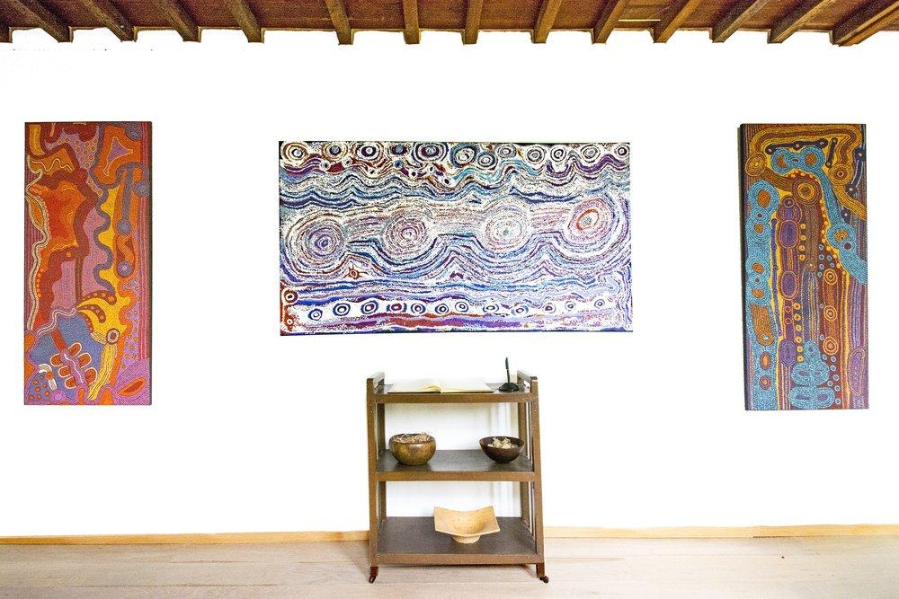 "Vue de l'exposition d'art Aborigène ""Inuntjii – Regeneration"" avec les artistes d'Ernabella.. A gauche et à droite, deux œuvres de l'artiste Unurupa Kulyuru (Titre : Minyma kutjara - Near Ernabella. Format : 150 x 68 cm). Au centre : une peinture de l'artiste Tjariya (Nungalka) Stanley (Titre : Minyma Kutjara Wingellina. Format : 180 x 100 cm). Photo : Aboriginal Signature • Estrangin gallery with the courtesy of the artists and Ernabella Arts."